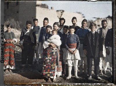 Groupe d'hommes, de femmes et d'enfants, au milieu des décombres